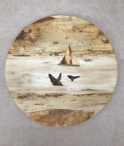 "a 12"" round wall hanging made of various barks a sailboat, whale tail, and a breaching whale"