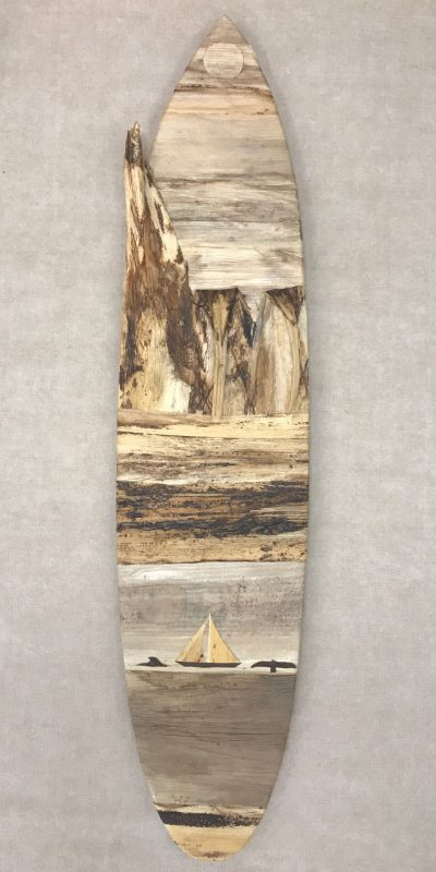 a large surfboard shaped wall hanging made of various colored barks measuring about 9x40 inches. A sun or moon at the top with a sailboat and 2 whale figures towards the bottom