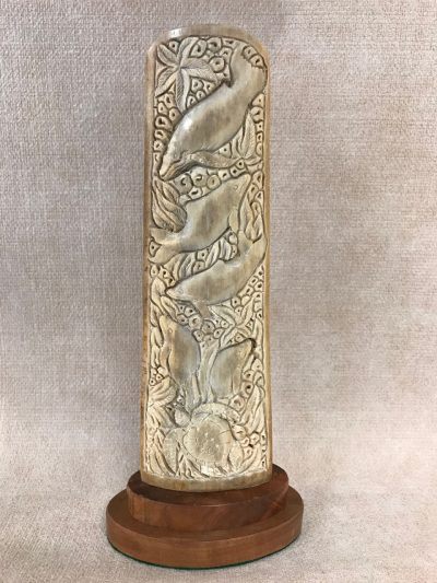 A tall carving made out of a swordfish bill. Dolphin and Turtle design front