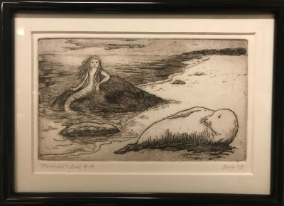 an original print of a mermaid and seal lying on the shore of a beach