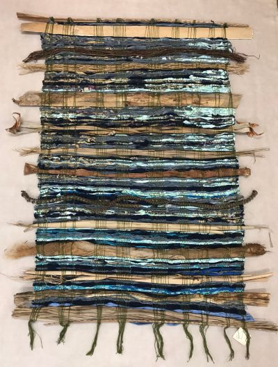 hand weaved wall hanging made of various fabrics and natural fibers. Blues, natural greens