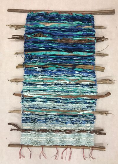 hand weaved wall hanging made of various fabrics and natural fibers. Various shades of blues. Light, sky blue, dark navy blue, white.