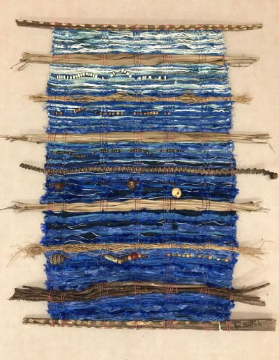hand weaved wall hanging made of various fabrics and natural fibers. Various colors of blue from light shades at the top to deep blues at the bottom. Beads and natural Hawaiian nuts incorporated into the weaving