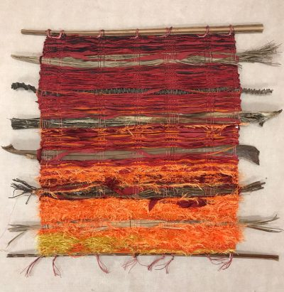 hand weaved wall hanging made of various fabrics and natural fibers. Reds and orange fabrics and yarn to resemble lava.