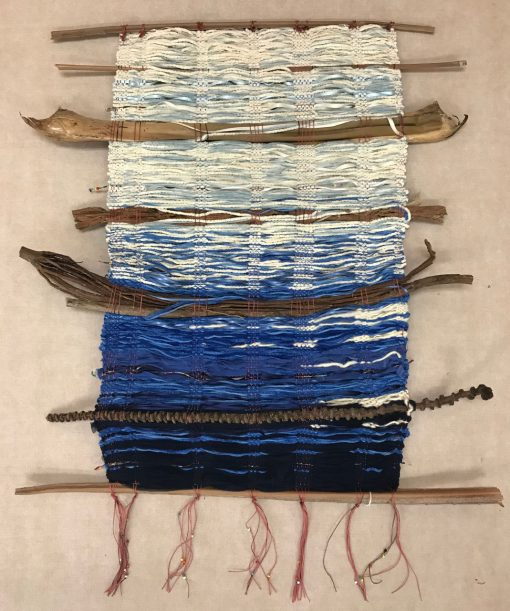 hand weaved wall hanging made of various fabrics and natural fibers. Starting with white at the top and changing to deep blues towards the bottom. Pink strings with beads hanging from the bottom.