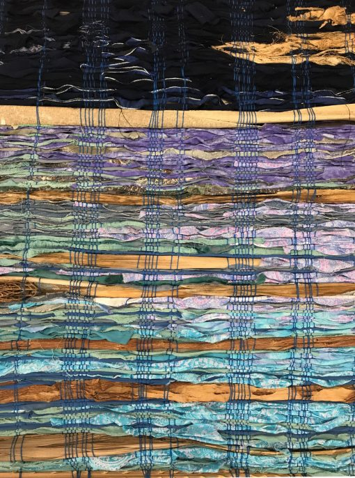 hand weaved wall hanging made of various fabrics and natural fibers. Dark and light blues with violet pieces of fabric, woven with royal blue thread