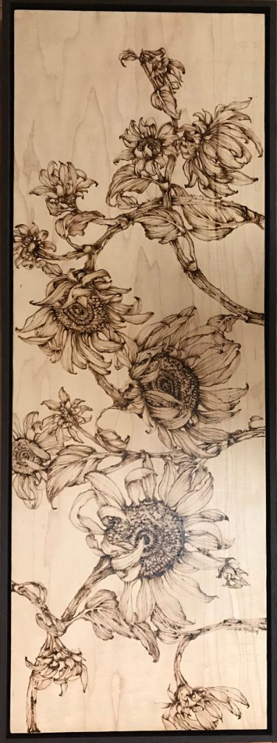 an original wood burned wall hanging of many sunflower plants. hung vertically