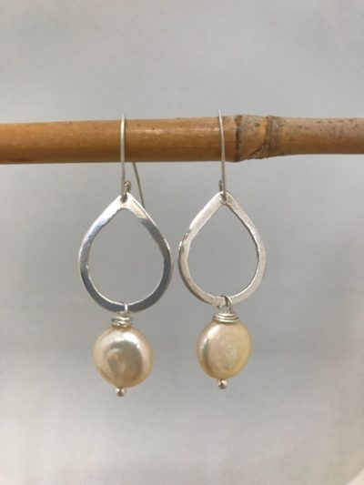 sterling silver teardrop shaped earrings with white, cream colored coin pearls hanging from the base. Sterling silver ear wires