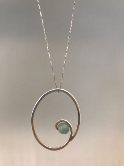 a sterling silver circular necklace with a swirl in the center and a sea foam green round glass bead. On a sterling silver chain