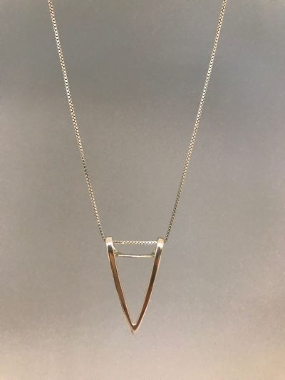 a sterling silver triangle pendant with the point facing down, on a sterling silver chain.
