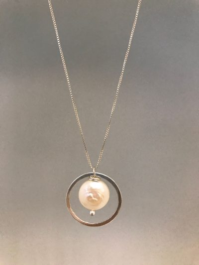 a sterling silver circle pendant with a coin pearl hanging in the center of the circle. On a sterling silver chain.