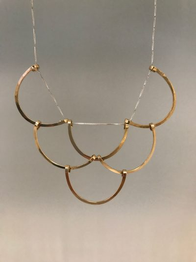 six gold filled half circles woven together to resemble fish scales hanging from a sterling silver chain