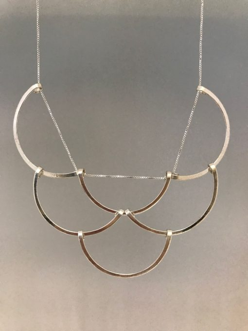 six sterling silver half circles woven together to resemble fish scales hanging from a sterling silver chain