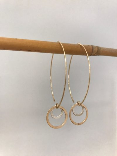gold filled oval shaped ear wires with a larger gold filled circle and a smaller sterling silver circle dangling from the base