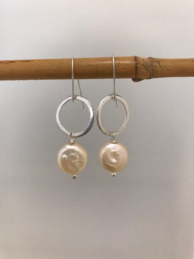 dime shaped sterling silver circle earrings with a single pink gold pearl hanging from the base. On Sterling silver ear wires