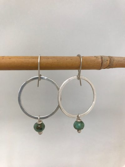 sterling silver circle earrings with a single small round piece of turquoise hanging from the bottom. On sterling silver ear wires.