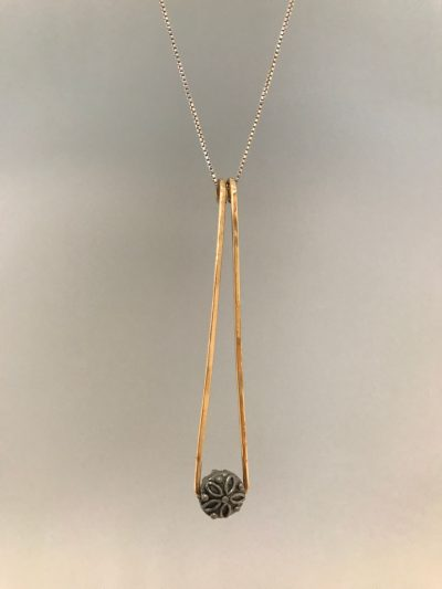 an elongated gold filled triangle with the point facing up, and a flower pewter bead at the bottom. On a sterling silver chain