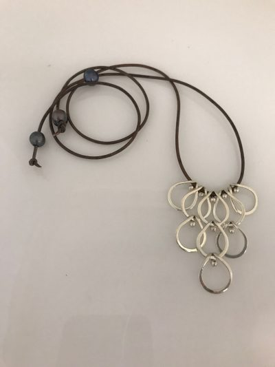 Nine sterling silver teardrop pendants hanging from a brown leather cord. Adjustable length with a Tahitian Pearl, and two additional pearls at each end of the leather cord
