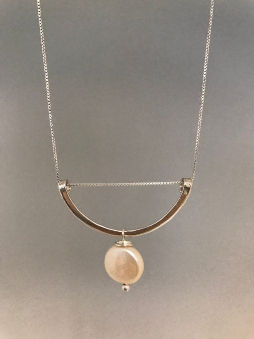 a sterling silver half circle with the open side facing up and a single pink coin pearl hanging from the center of the curved edge. On a sterling silver chain.