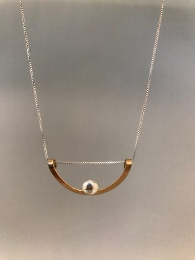 a gold filled half circle, with the open end facing up. A single sterling silver ball in the center of the curved side of the half circle. On a sterling silver chain.