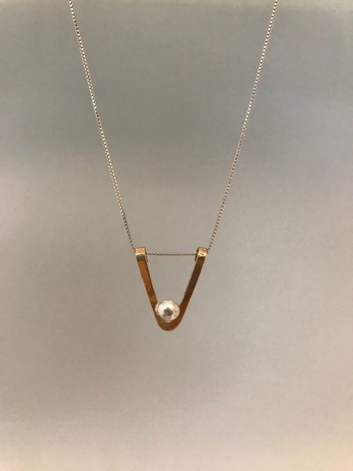 a gold filled triangle, with the point facing down, and a single sterling silver ball at the point. On a sterling silver chain