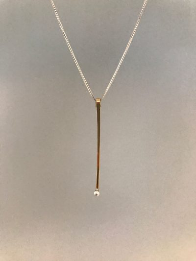 a single gold filled straight pendant with a sterling silver dot at the end. On a sterling silver chain
