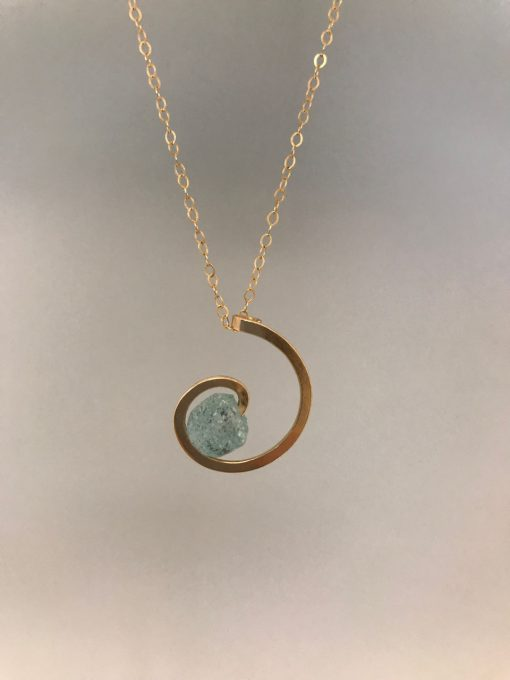 a gold filled swril pendant with a seafoam green round piece of sea glass in the center. On a gold filled chain