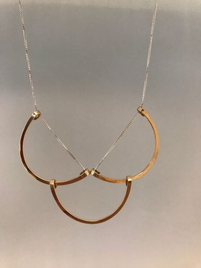 Three gold filled half circle pendants strung together at the end of a sterling silver chain