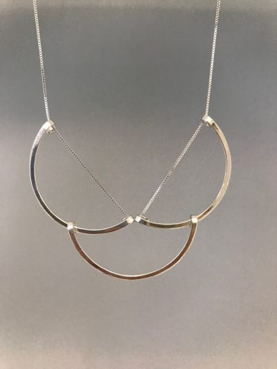 Three sterling silver half circle pendants strung together at the end of a sterling silver chain