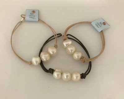 bracelet with a magnetic clasp. Leather cord, tan or dark brown, three white pearls.