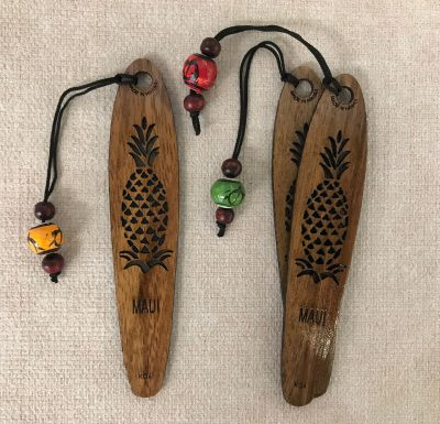 "a bookmark made of Hawaiian Koa Wood. A single pineapple plant carved out of the center with the word ""Maui"" below it"