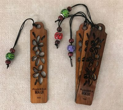 "a bookmark made of Hawaiian Koa Wood. Plumeria flowers cared out of the entire bookmark. The word ""Maui"" at the bottom"