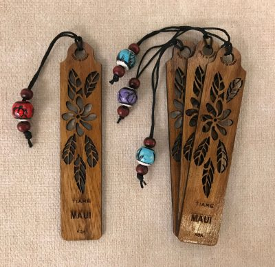 "a bookmark made of Hawaiian Koa Wood. A single Tiare flower carved out of the center with five tiare plant leaves surrounding the flower. The Word ""Maui"" etched beneath it"