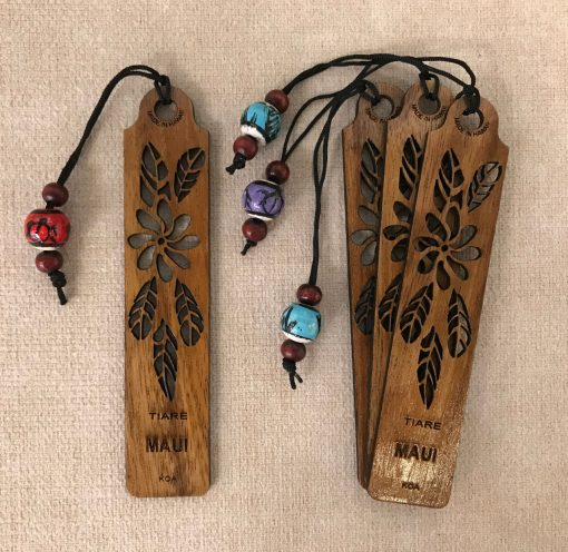"""a bookmark made of Hawaiian Koa Wood. A single Tiare flower carved out of the center with five tiare plant leaves surrounding the flower. The Word """"Maui"""" etched beneath it"""