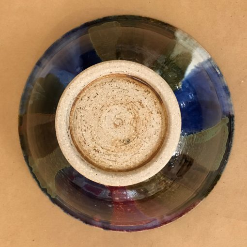 back of a large ceramic serving bowl. Deep, earthy colors.