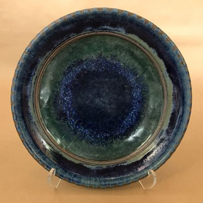 a large ceramic serving bowl which is mostly navy blue with some deep green hues.
