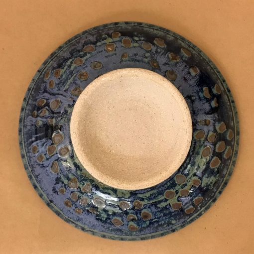 back of a large ceramic serving bowl. Blue hues and brown speckled dots