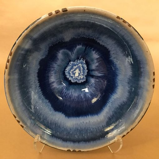a ceramic serving bowl with a blue tie-dye looking design. Light blue, dark blue, and a white center