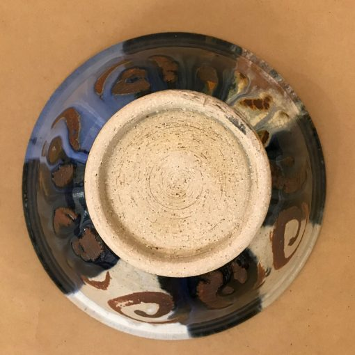 the back of a large ceramic serving bowl with black, blue, white, and tan blocks of color. Brown spirals around the entire rim.