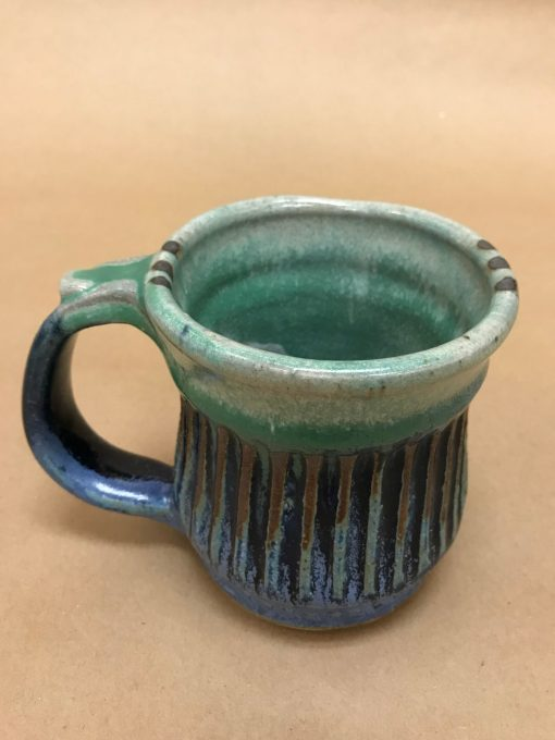 a large ceramic mug made of various blue hues, some brown colors, and aqua. Ribbed design and a thumb rest