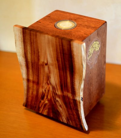 a wooden box made of Koa and Mahogany wood. The lid of the box is facing front and has organic edges. The top of the box has an coin inlayed.