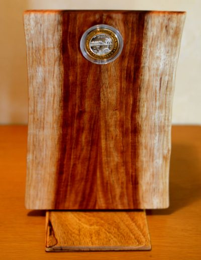 a wooden box made of Koa and Mahogany wood. The lid of the box is facing front and has organic edges. The front of the box has an coin inlayed.