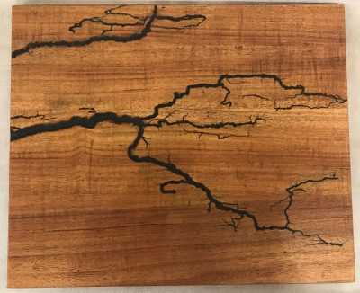 a original wall hanging made of Hawaiian Koa wood. Socked with electricity to form an organic design. Outline of electrical waves is black, against the wood grains.