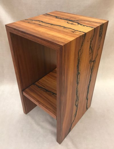 a stand, or shelf made of Hawaiian Koa and Wenge wood. Shocked with electricity to form an organic design. Side View
