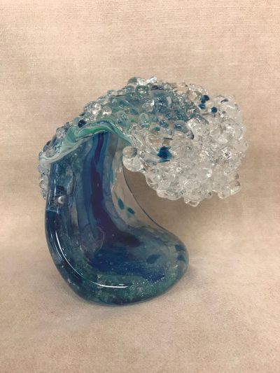 a blown glass wave sculpture. Standing about 7 inches tall. mostly blue colored, various shades of blue, and clear, to resemble the foam of a wave.