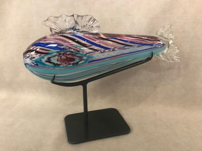 a blown glass reef fish made up of various shades of blue, magenta, white and black. With a stand to allow the fish to hang horizontally. Facing left
