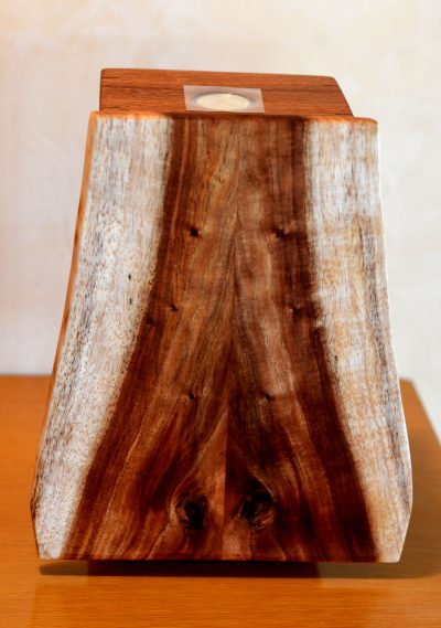 a wooden box made of Koa and Mahogany woods. The box is a rectangular shape, traditional. While the front lid is organic in color and shape.