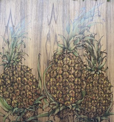 three pineapples woodburned and oil painted onto a teak wood panel.