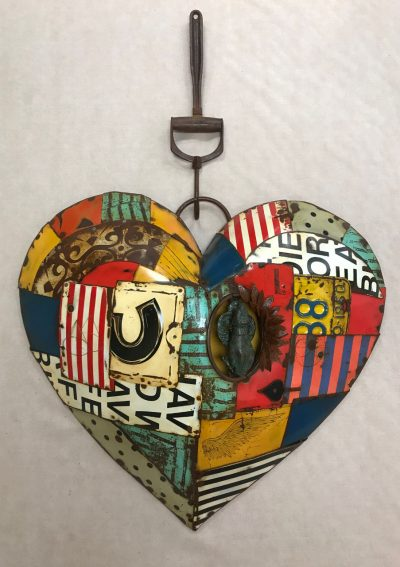 a two piece metal wall hanging made of recycled metals. Heart is made of various colors and textures and the holder is a single piece.