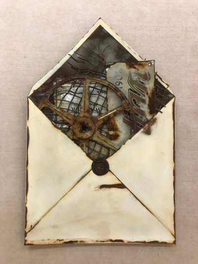 a recycled metals sculpture of an open envelope filled with various items.